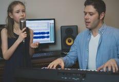 Man med lilla flickan i musikstudio Arkivfoto