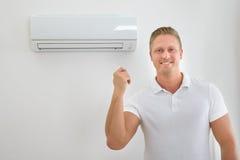 Man med luftkonditioneringsapparatfjärrkontroll royaltyfri bild