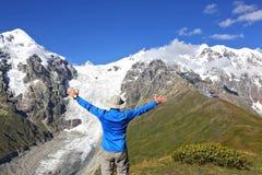 Man med lyftta händer som står på bakgrunden av den snöig mountaen Arkivfoto