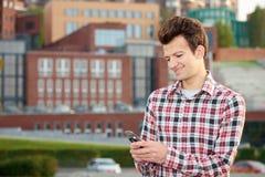 Man med mobiltelefonen utomhus Fotografering för Bildbyråer