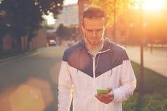 Man med mobiltelefonmaskinskrivningtext, ljus sol på gatan Arkivfoton