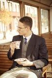 Man med mustaschen och exponeringsglas på drevträvagnen som dricker cof Arkivfoton