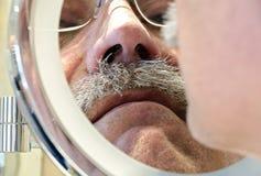 Man med mustaschen som ser in i en raka spegel Royaltyfria Bilder