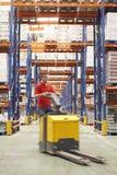 Man med paletten Jack Through Warehouse Royaltyfri Fotografi