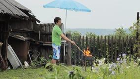 Man med paraplyet nära branden för grillfest Regnet faller, en gammal byggnad med ett staket i bakgrunden arkivfilmer
