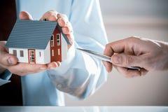 Man med Pen Pointing Miniature House av ett medel royaltyfri bild