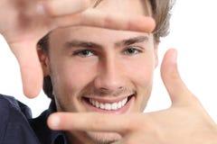 Man med perfekt vitt leende som inramar framsidan med händer arkivbilder