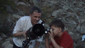 Man med pojken som använder teleskopet arkivfilmer