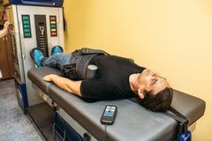 Man med problem av den ryggrads- bråck för bottenlägebaksida på sträcknings- och dykarsjukatillvägagångssätt i vårdcentralen, ort royaltyfri foto