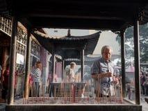 Man med rökelse som ber på den kinesiska templet Arkivfoto