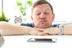 Man med roligt ansiktsuttryck som stirrar på mobiltelefonen royaltyfri bild
