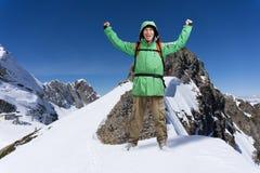 Man med ryggsäckanseende på snöig berglutning Alpinist- eller bergfotvandrare Arkivfoton