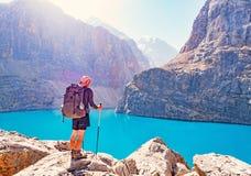 Man med ryggsäcken nära sjön stor Alo på bakgrund för stenigt berg Fann Mountains arkivfoto