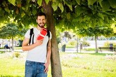 Man med ryggsäcken och en gåva bredvid ett träd fotografering för bildbyråer