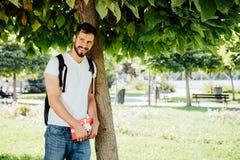 Man med ryggsäcken och en gåva bredvid ett träd Royaltyfri Fotografi