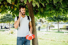 Man med ryggsäcken och en gåva bredvid ett träd royaltyfri foto