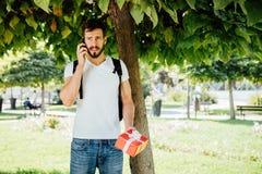 Man med ryggsäcken och en gåva bredvid ett träd arkivbild