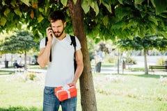 Man med ryggsäcken och en gåva bredvid ett träd arkivfoton