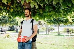 Man med ryggsäcken och en gåva bredvid ett träd royaltyfria bilder