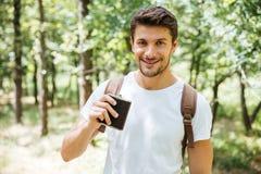 Man med ryggsäcken och flaskan som går i skog Royaltyfri Foto