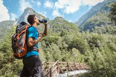 Man med ryggsäcken som dricker från vattenflaskan som omges, genom att göra häpen naturen royaltyfri bild