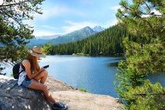 Man med ryggsäcken som fotvandrar i berg på en tur för sommarsemester fotografering för bildbyråer