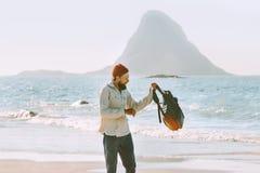 Man med ryggsäcken som går på havstranden arkivfoton