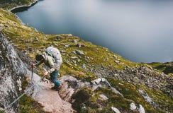 Man med ryggsäcken som klättrar upp att rymma kedjor till bergtoppmötet arkivfoto