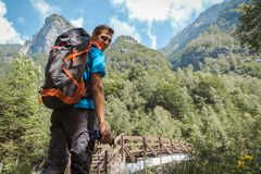 Man med ryggsäcken som ler till kameran som omges, genom att göra häpen naturen och berg royaltyfria foton