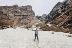 Man med ryggsäcken som trekking i berg Kallt väder, snö på kullar fotvandra magiskt trä för restkortslutningsvinter royaltyfria foton