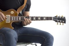 Man med sammanträde för elektrisk gitarr som isoleras över vit fotografering för bildbyråer