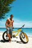 Man med sandcykeln på stranden som tycker om sommarloppsemester Royaltyfria Bilder