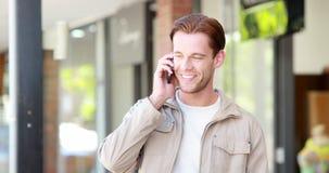 Man med shoppingpåsar som svarar hans telefon lager videofilmer