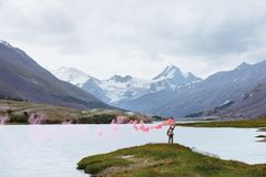 Man med signalbrand på bakgrund av bergsjön royaltyfri fotografi