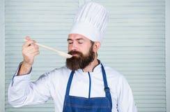 Man med skägget i kockhatt- och förklädehåll som lagar mat hjälpmedel Laga mat som yrkesmässig ockupation Skäggig kockhåll för Hi royaltyfri foto