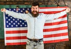 Man med skägget och mustasch på lycklig framsidahållflagga av USA, träbakgrund Den amerikanska läraren rymmer amerikanska flaggan Royaltyfria Bilder