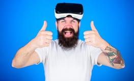 Man med skägget och mustaschen med VR-exponeringsglas, blå bakgrund Grabb med VR-exponeringsglas eller head monterad skärm VR-tek Arkivfoto