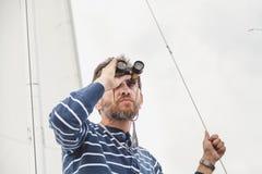 Man med skägget som ser till och med kikare som seglar yachten Royaltyfria Bilder