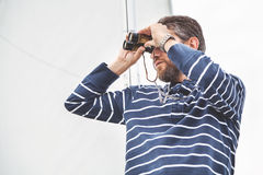 Man med skägget som ser till och med kikare som seglar yachten Royaltyfri Fotografi