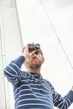 Man med skägget som ser till och med kikare som seglar yachten Arkivbilder