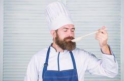 Man med sk?gget i kockhatt- och f?rkl?deh?ll som lagar mat hj?lpmedel Laga mat som yrkesm?ssig ockupation Sk?ggig kockh?ll f?r Hi royaltyfri foto