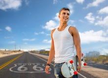 Man med skateboarden över oss bakgrund för rutt 66 Fotografering för Bildbyråer