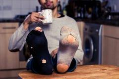 Man med slitna ut sockor som har kaffe i kök Fotografering för Bildbyråer