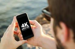 Man med smartphonen för upplösning 4k på kusten Arkivfoto