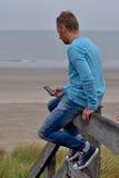 Man med smartphonen på stranden arkivbild