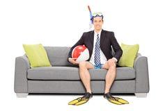 Man med snorkeln och affärsdräkt som placeras på soffan Arkivbild