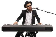 Man med solglas?gon och ett sk?gg som spelar ett digitalt piano och sjunger p? en mikrofon royaltyfri foto