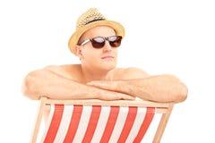 Man med solglasögon som sitter på en soldagdrivare Royaltyfri Bild