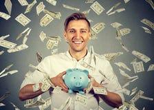 Man med spargrisen under pengarregn som ner faller dollarräkningar Royaltyfri Bild