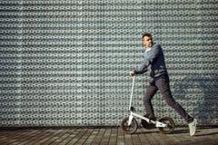 Man med sparkcykeln framme av byggnaden royaltyfria foton